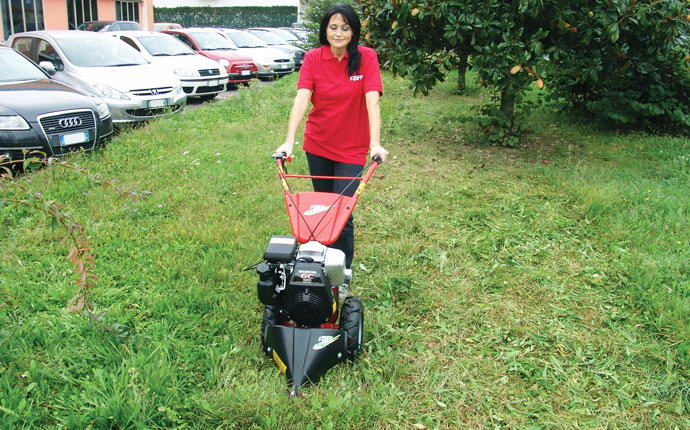 Girl cut the lawn with motormower Fort Micro 2000.