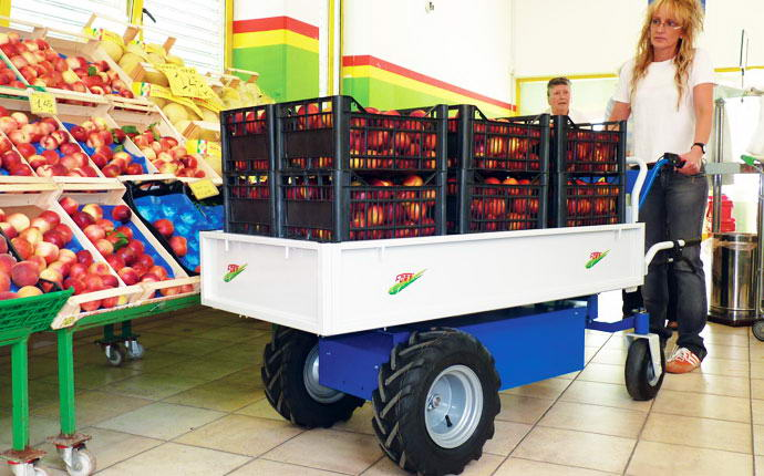 Electric transporter 600 WXL Fort, lady driving with load boxes of peaches in a supermarket fruit.